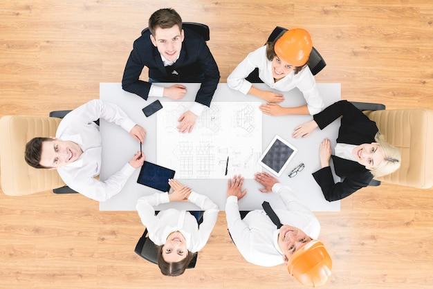 Gli ingegneri felici lavorano con un disegno sul tavolo. vista dall'alto