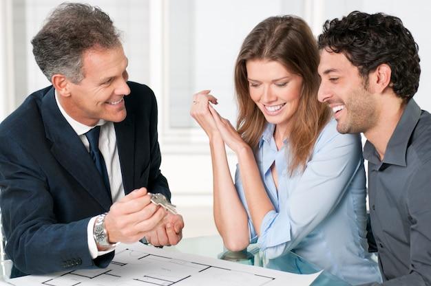 Felice agente immobiliare che mostra le nuove chiavi di casa a una giovane coppia dopo una discussione sui piani della casa.