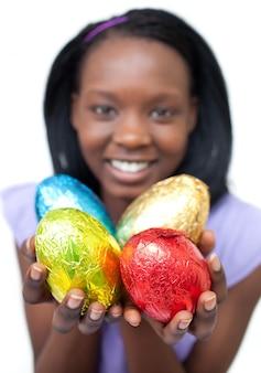 Donna etnica felice che mostra le uova di pasqua