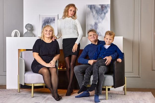 La famiglia europea felice è seduta vicino al caminetto elettrico decorativo nel soggiorno.