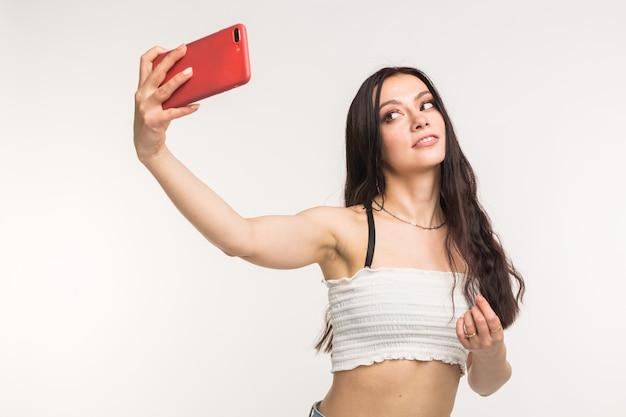 Modello femminile europeo felice con capelli scuri che gode del servizio fotografico dell'interno. la giovane donna sta prendendo un selfie sulla superficie chiara.