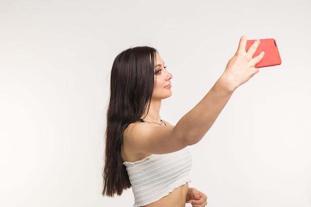 Modello femminile europeo felice con capelli scuri che gode del servizio fotografico dell'interno