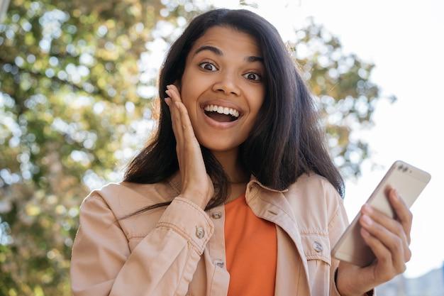 Felice eccitata donna afro-americana utilizzando il telefono cellulare, acquisti online