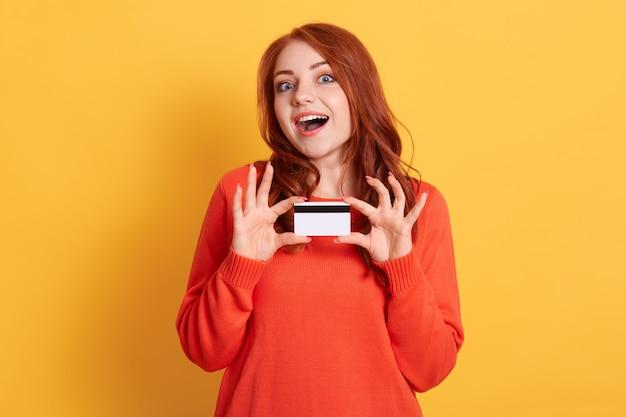 Giovane donna stupita eccitata felice che tiene la carta di credito nelle mani e che guarda direttamente con la bocca ampiamente aperta