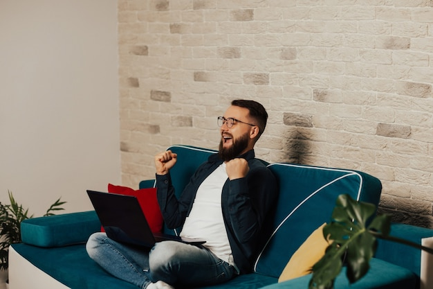 Felice eccitato uomo barbuto in occhiali seduto sul divano blu con il computer portatile a casa. celebra la vittoria online