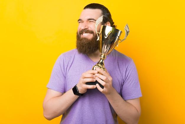 L'uomo barbuto eccitato felice sta abbracciando il suo trofeo d'oro.