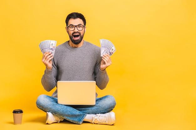 Uomo casuale eccitato felice che si siede sul pavimento con il computer portatile e che tiene i soldi isolati sopra fondo giallo.