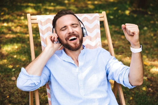 Felice eccitato emotivo giovane uomo barbuto ascoltando musica