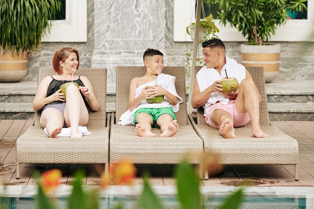 Felice eccitato padre, madre e figlio seduti su sedie a sdraio e bevendo deliziosi cocktail al cocco