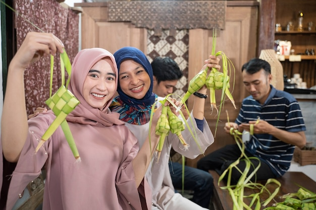 Felice gruppo entusiasta di amici e familiari che fanno ketupat insieme per eid fitr mubarak o idul fitri lebaran tradizione