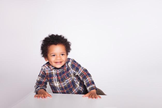 Il ragazzino afroamericano emozionante felice in abbigliamento casual sta proponendo isolato su bianco