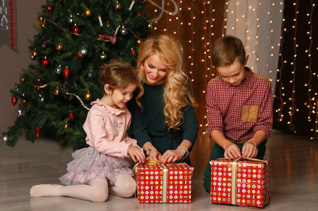Genitori emozionati felici che guardano come la figlia apre il regalo di natale.