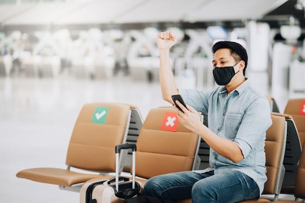 Felice viaggiatore eccitato uomo asiatico con bagagli che indossa la maschera per il viso utilizzando il telefono cellulare e alzando il braccio per celebrare il successo o il risultato.