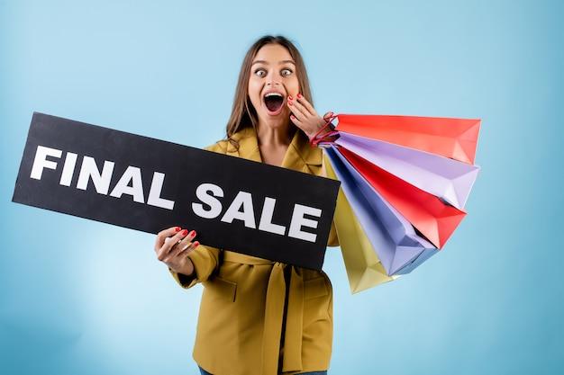 Segno emozionante felice di vendita del nero del copyspace della tenuta della donna e sacchetti della spesa variopinti isolati sopra il blu