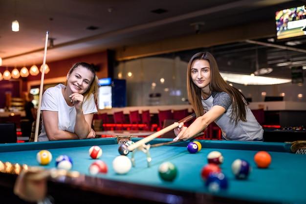 Donne felici ed emozionate che giocano a biliardo insieme