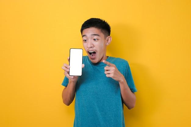 Felice eccitato giovane uomo asiatico shock che punta lo schermo del telefono vuoto per lo spazio della copia e che mostra lo schermo del telefono bianco alla fotocamera, isolato su sfondo giallo