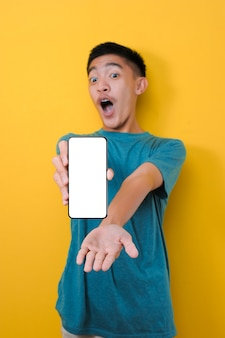 Felice eccitato giovane uomo asiatico shock che mostra lo schermo del telefono bianco alla fotocamera, isolato su sfondo giallo