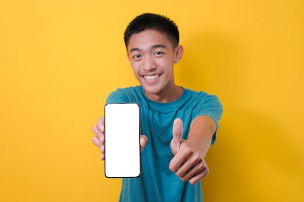Felice eccitato giovane uomo asiatico che mostra lo schermo del telefono bianco alla fotocamera con il pollice in su, isolato su sfondo giallo