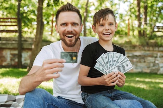 Giovane padre emozionante felice che si siede con il suo piccolo figlio che tiene soldi e carta di credito.