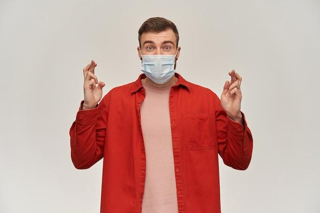 Felice eccitato giovane uomo con la barba in camicia rossa e maschera igienica per prevenire l'infezione tiene le dita incrociate per esprimere un desiderio sul muro bianco