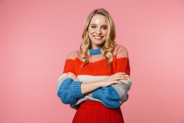Una giovane donna abbastanza bella eccitata felice in posa isolata su un muro rosa