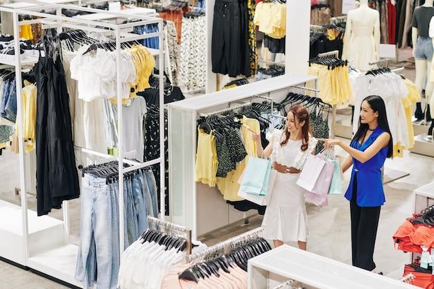 Giovani donne vietnamite eccitate felici alla ricerca di vestiti nuovi nel grande magazzino