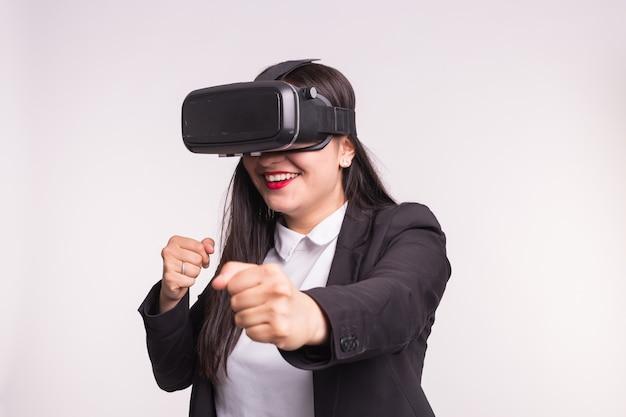 Felice giovane donna eccitata utilizzando un auricolare per realtà virtuale sul muro bianco