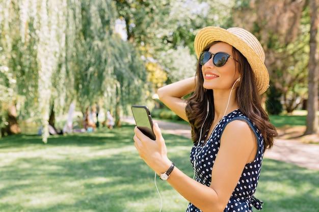 Felice donna uscita ascoltando musica e godersi l'estate nel parco
