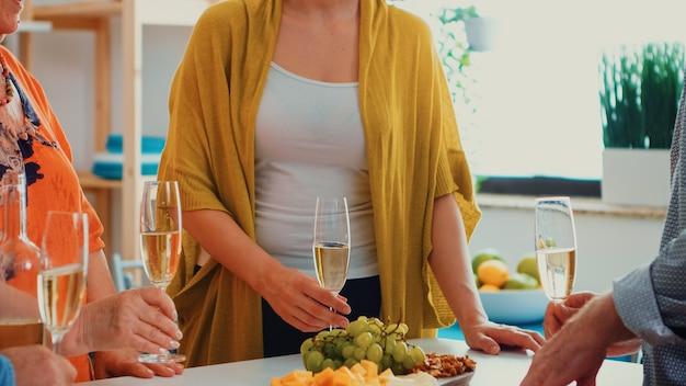 Famiglia allargata felice che gode di un bicchiere di champagne di vino. persone di due generazioni che parlano, sedute intorno al tavolo brindando e festeggiando un evento bevendo un bicchiere di vino bianco.