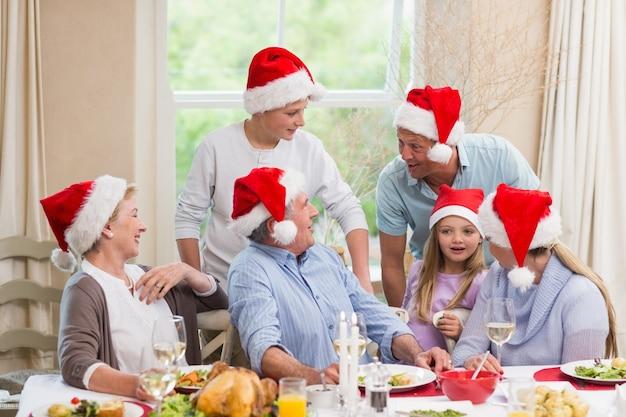 Famiglia allargata felice in cappello della santa che parla insieme