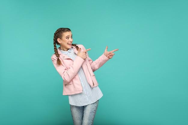 Faccia felice che indica copyspaceportrait di bella ragazza carina in piedi con trucco e acconciatura di codino marrone in camicia a righe blu giacca rosa. studio al coperto isolato su sfondo blu o verde