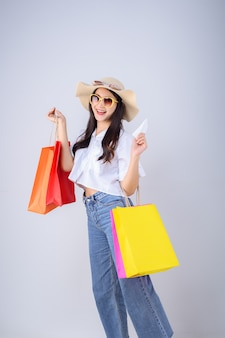 Faccia felice e sorriso di giovane donna asiatica che tiene un colore e una fattura del sacchetto della spesa su fondo bianco.
