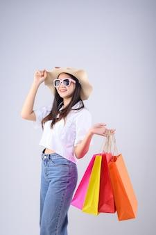 Faccia felice giovane donna asiatica in possesso di un sacchetto della spesa, con indosso un cappello e occhiali isolati su sfondo bianco.