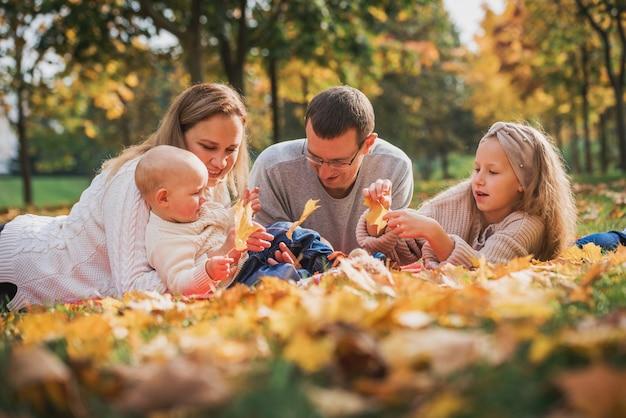 Famiglia felice in un parco in autunno