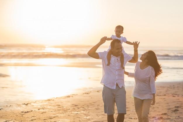 Famiglia felice e bambino che godono del tramonto nello svago di estate