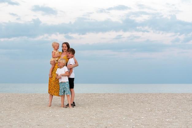 Famiglia felice sulla spiaggia. mamma e tre bambini che si divertono sul mare. stile di vita familiare.
