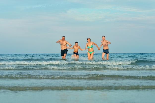 Famiglia felice in spiaggia in estate contro il cielo