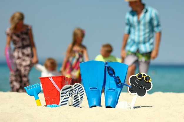 Famiglia felice sulla spiaggia con pinne e giocattoli