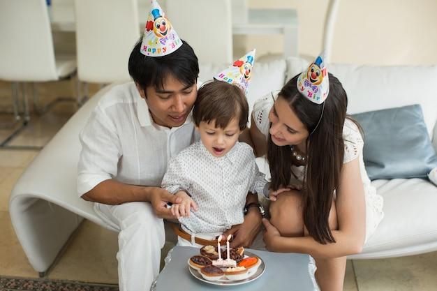 Famiglia felice che soffia candele insieme per un compleanno a casa