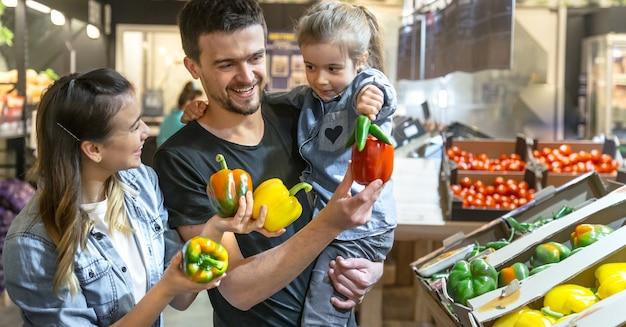 La famiglia felice compra le verdure. una famiglia allegra di tre carte che scelgono nel reparto ortaggi.