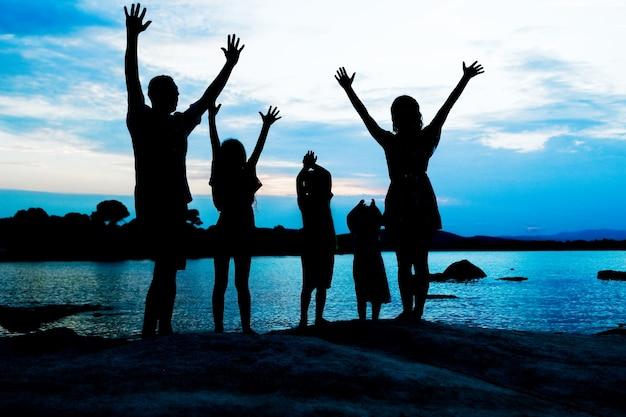 Famiglia felice in riva al mare sulla silhouette della natura