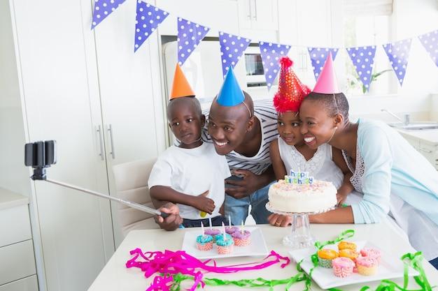 Famiglia felice che celebra insieme un compleanno e prendendo un selfie