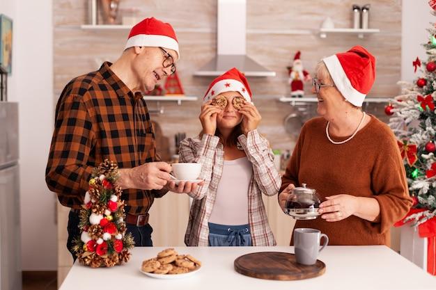 Famiglia felice che celebra le vacanze di natale trascorrendo del tempo insieme in una cucina decorata per natale