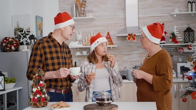 Famiglia felice che celebra insieme le vacanze di natale mangiando deliziosi biscotti al cioccolato