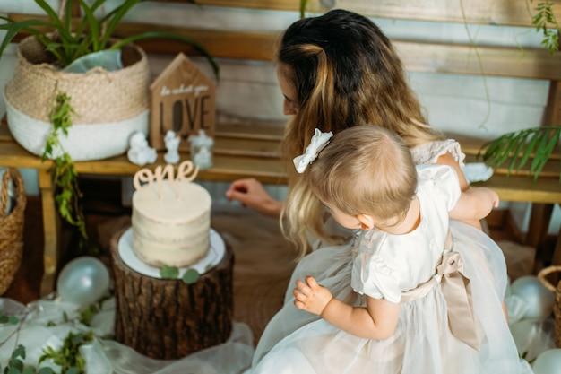 Famiglia felice che festeggia il primo compleanno della figlia con la torta idee per la festa di compleanno a casa con
