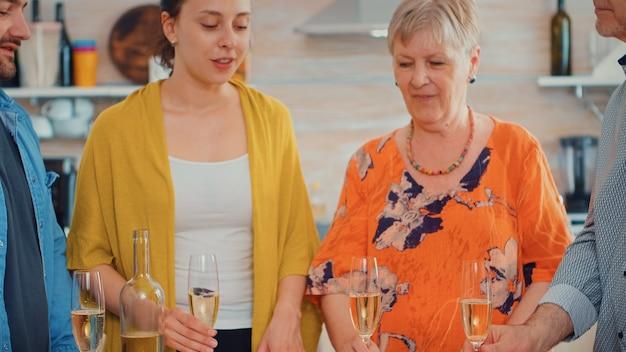 Famiglia felice che celebra a casa allietando un bicchiere di champagne. persone di due generazioni che parlano, sedute intorno al tavolo brindando e festeggiando un evento bevendo un bicchiere di vino bianco.