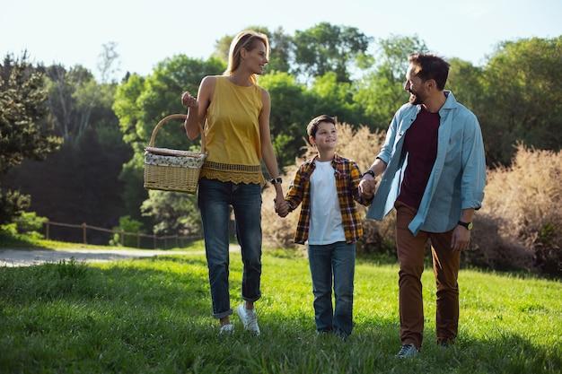 Famiglia felice. madre bionda allegra che tiene un cestino e che fa una passeggiata con la sua famiglia