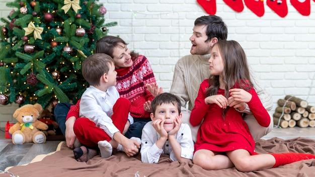Famiglia felice in abiti natalizi sul pavimento vicino all'albero di natale a casa. idea di famiglia felice