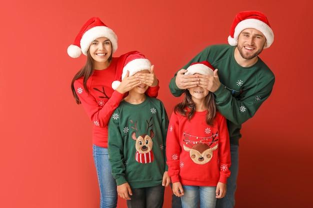 Famiglia felice in maglioni di natale e cappelli di babbo natale su rosso
