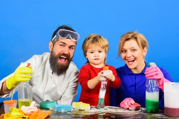 Famiglia felice che pulisce insieme una giornata pulita giocando con la disinfezione della spugna degli strumenti di pulizia